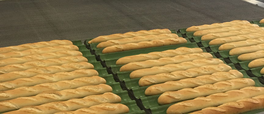 Baguette on the trays baked in the mesh-belt oven of Alitech Srl