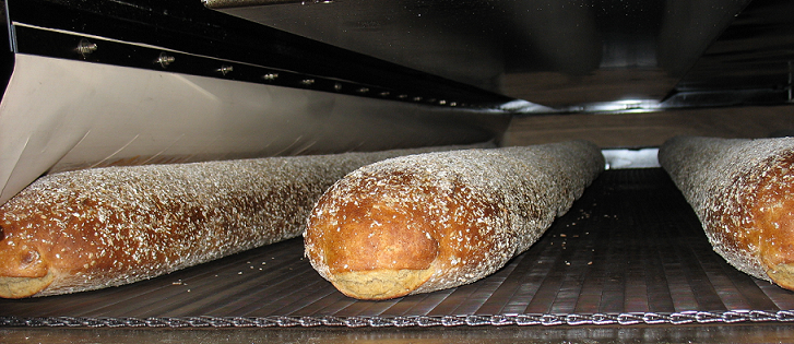 Bread on the mesh-belt inside the tunnel oven Alitech Srl