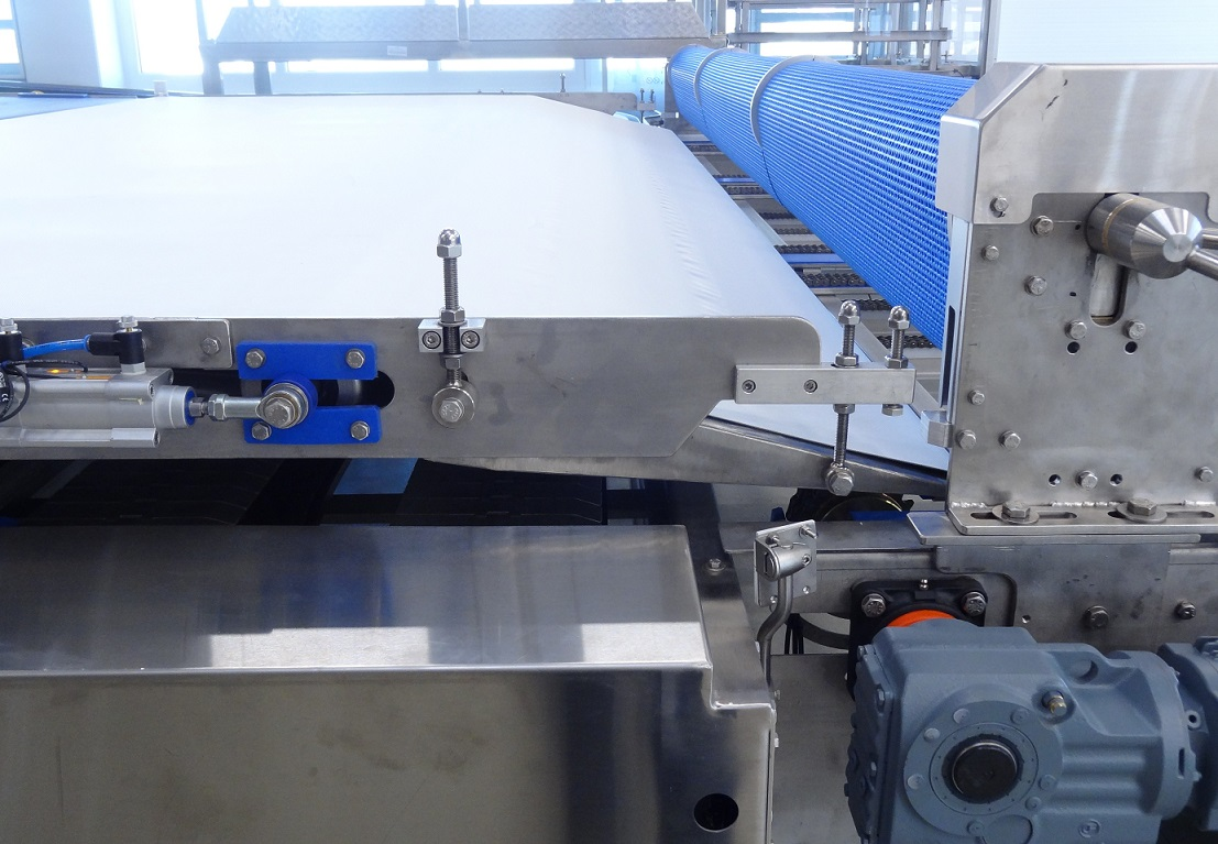 Stripping conveyor to collect product from trays